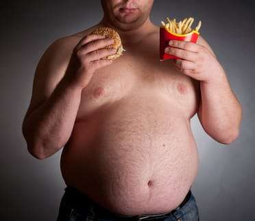 overweight man eating chips