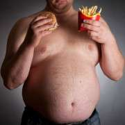 obese man eating a burger