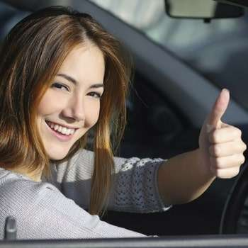 woman driving confidently and giving thumbs up