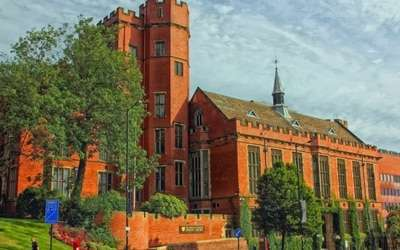A red brick university building surrounded by trees