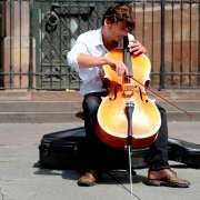 A man playing a cello outside